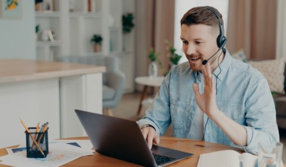 Smiling male freelancer working at home and using headset while looking at laptop screen and saying hello, waving to somebody and smiling, sitting in front of computer and having video call (Smiling male freelancer working at home and using headset wh